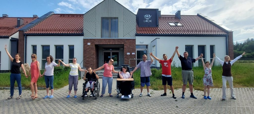 grupa radosnych osób przed domem