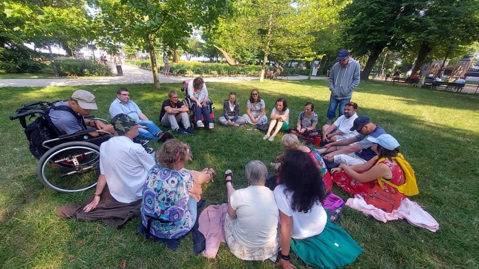 ludzie siedzą na trawie